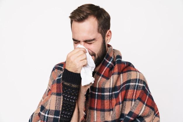 Портрет больного кавказского парня, завернутого в одеяло, чихающего и держащего бумажную салфетку из-за гриппа, изолированного на белой стене