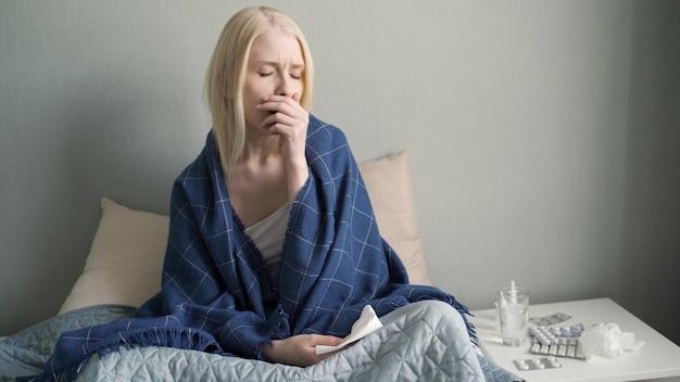 Портрет больной женщины дома. молодая женщина кашляет в спальне.