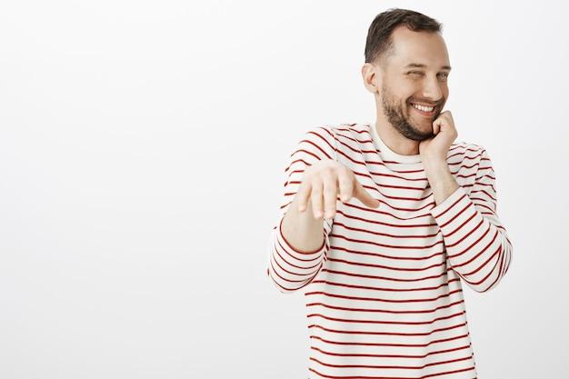 Портрет нетерпеливого довольного симпатичного парня-гея в полосатой рубашке, краснеющего, пока мужчина делает предложение, хихикает от смущения и застенчиво, тянет ладонь, чтобы надеть кольцо на палец