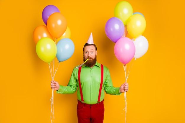 印象的な面白いファンキーな紳士の肖像画は、お祝いパーティーの誕生日を準備します空気ヘリウムボールを吹くノイズメーカーピンクの点線のコーンを着用鮮やかなパンツズボン孤立したすね色