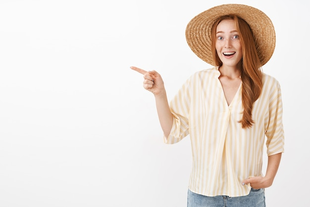 麦わら帽子のそばかすと縞模様の夏のブラウスを左に向けて感動と興奮の女性らしい臆病な赤毛の女性の肖像画