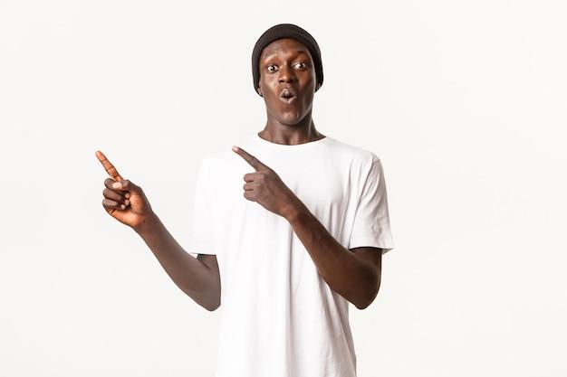 Портрет впечатленного и удивленного афро-американского парня в шапочке, указывающего пальцами в верхнем левом углу с удивленным, удивленным лицом
