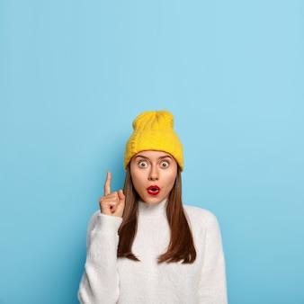 感動したブルネットの少女の肖像画は人差し指で上を示し、不思議からあえぎます