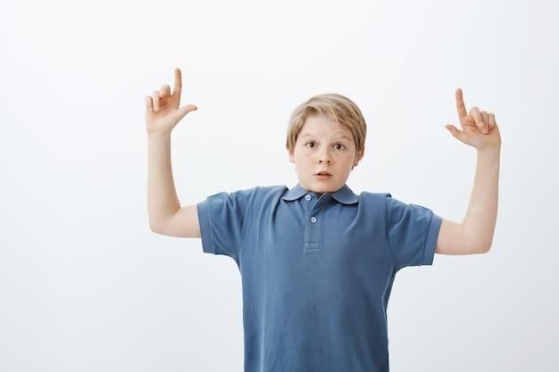 Портрет впечатленного возбужденного молодого европейского мальчика со светлыми волосами, поднимающего указательные пальцы и указывающего вверх, удивляясь и поражаясь