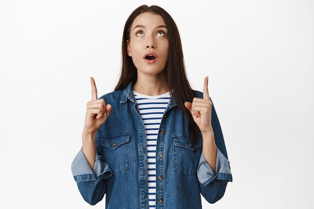 白地にスリル満点の表情で指を上に向けて見つめている感動した女の子のあえぎの肖像画
