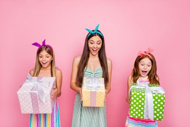 Портрет впечатленных девушек с ободками брюнетки, кричащими вау, боже, получают подарки в ярком платье-юбке, изолированном на розовом фоне