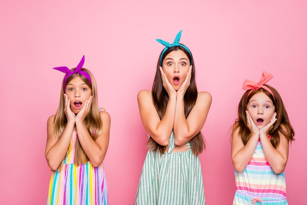 ピンクの背景に分離されたドレススカートを身に着けているニュースを聞いて彼らの頬に触れてomgを叫んで色のヘッドバンドで感銘を受けた女の子の肖像画
