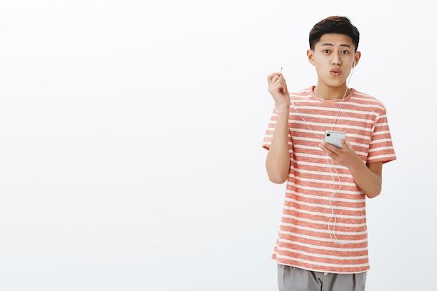 스마트 폰을 통해 음악을 듣는 즐거움과 기쁨을 표현하기 위해 이어 버드를 벗고 새로운 이어폰을 사용하는 감동적인 잘 생긴 젊은 아시아 십대의 초상화