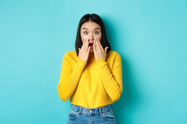 青い背景の上に黄色のプルオーバーで立って、すごい、あえぎ、カメラを見て驚いて見つめていると言って感動した韓国の女の子の肖像画