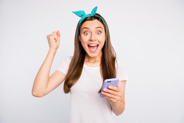 감동적인 긍정적 인 명랑 소녀의 초상화는 스마트 폰을 사용하여 온라인 대회에서 승리에 대한 알림을 받고 비명을 지르고 주먹을 들어 빈티지 스타일의 옷을 입습니다.