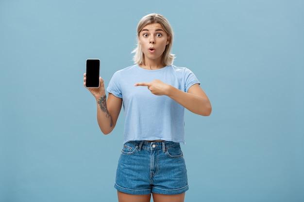 T- 셔츠와 데님 반바지에 감동 된 말문이 잘 생긴 젊은 운동가의 초상화가 와우 폴딩 입술이 스마트 폰을 보여주고 화면을 가리키는 파란색 벽을 가리키는
