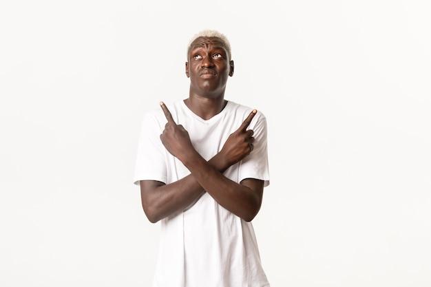 Портрет нерешительного афро-американского парня, принимающего решение, указывающего в сторону пальцами и растерянного
