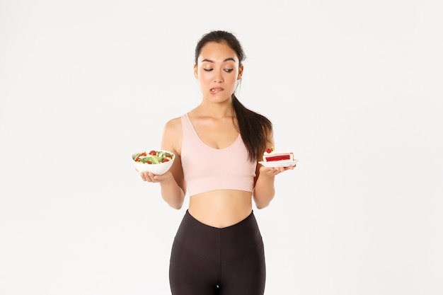 우유부단하고 유혹적인 귀여운 아시아 소녀의 초상화는 맛있는 케이크를 보면서 유혹에 저항하고 다이어트 중이며 건강한 샐러드를 먹을 필요가 있습니다.
