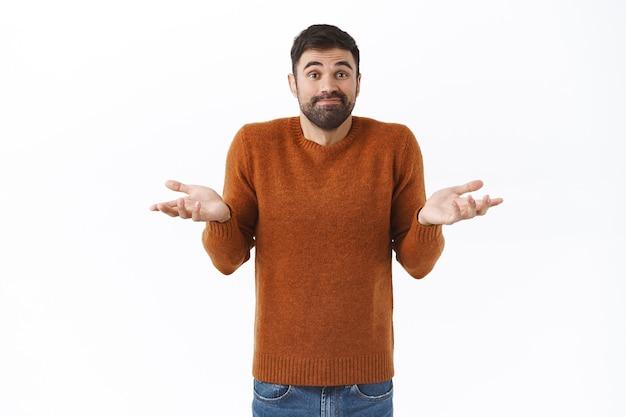 茶色のスウェットシャツを着た優柔不断で無知な魅力的なあごひげを生やした男の肖像、わからない、手を横に広げて無力に笑う、気づいていないように肩をすくめる、質問に答えるのに混乱する