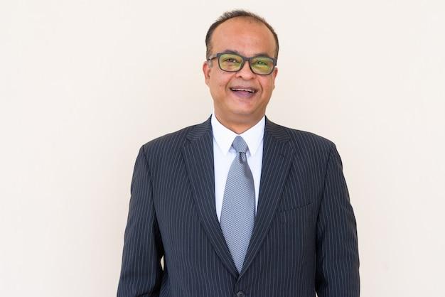 Портрет индийского бизнесмена, улыбающегося простой стене на открытом воздухе