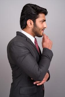 Портрет индийского бизнесмена, думая на сером фоне