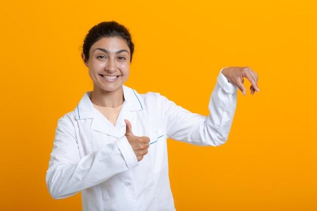 Портрет индийской женщины-врача в белом медицинском халате, держащей пальцами шаблон вакцины covid-19 или другого медицинского материала, изолированного на желтом фоне.