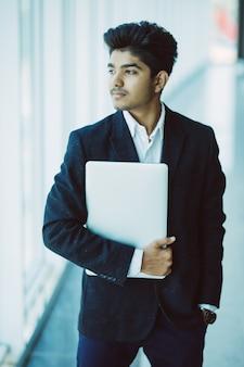 Портрет индийского счастливого бизнесмена используя портативный компьютер в офисе