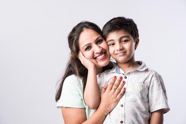 カメラを見て、白い背景の上のインドの若い母と息子の肖像画