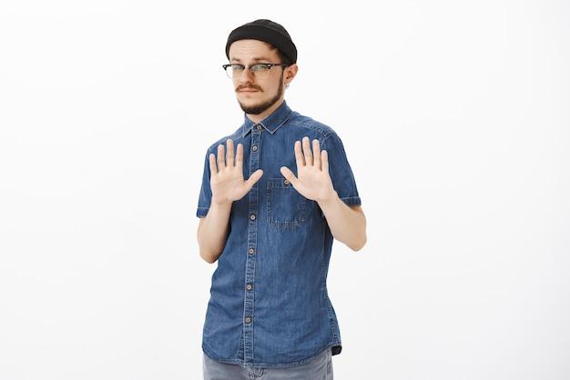 Портрет равнодушного и невпечатленного красивого стильного бородатого парня в очках и черной шапочке, поднимающего ладони в знак отказа и жестом отказа, не заинтересованного в странном предложении