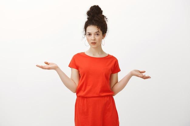 Портрет равнодушной беззаботной кавказской кудрявой женщины в красном платье, разводящей руками