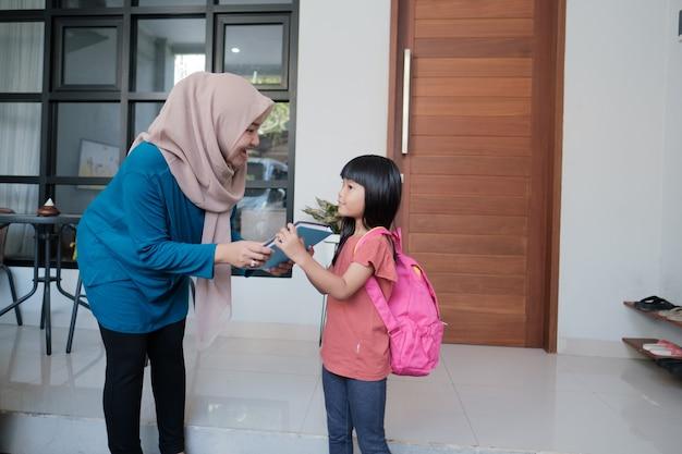インドネシアの小学校の女子学生の肖像画は、学校に行く前に彼女のイスラム教徒の母親の手を振ってキスします