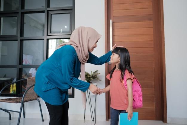 Портрет ученицы начальной школы из индонезии пожимает руку своей матери-мусульманке перед тем, как пойти в школу