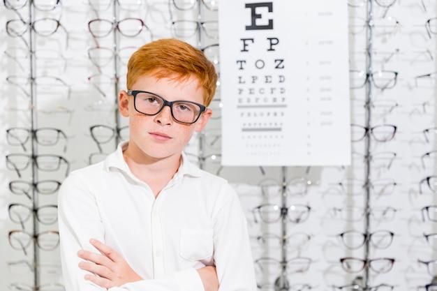 Портрет невинного мальчика со скрещенными руками позирует в магазине оптики