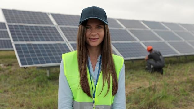 태양 전지 패널 필드에 서 있는 작업복에서 검사 엔지니어 여성의 초상화. 청정 에너지 생산. 친환경 에너지. 생태 태양광 발전소.