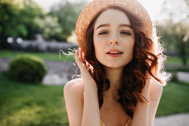 自然にポーズをとる夏の帽子でインスピレーションを得た生姜の女性の肖像画。晴れた日に笑顔の赤い髪の幸せな白い女性モデル。 無料写真