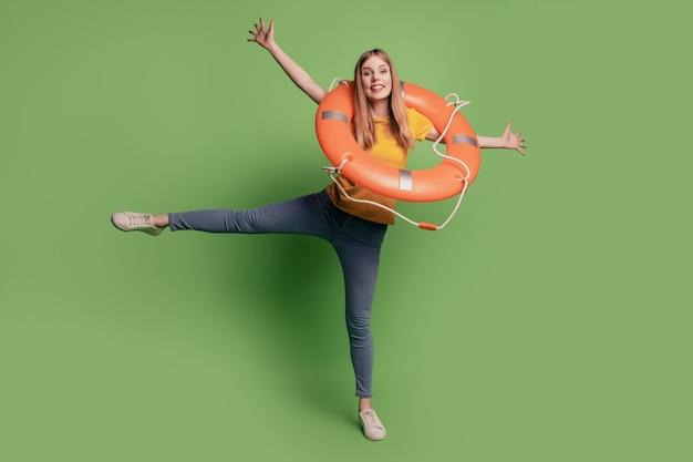영감을 받은 긍정적인 여성의 초상화는 녹색 배경에 노란색 티셔츠 청바지 신발을 신고 풍선 원 댄스를 들고 있습니다.