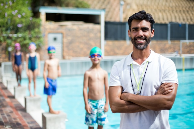 Портрет инструктора с детьми, стоящими на стартовом блоке