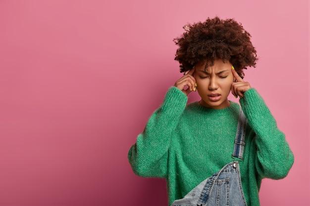 片頭痛のために目を閉じる強烈な絶望的な女性の肖像画