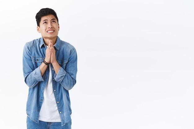 걱정스러운 젊은 아시아 남성의 초상이 꿈이 이루어지기 위해 초조하게 기도하고, 신과 이야기하고, 손을 잡고 하늘로 머리를 들고 기도하고, 구걸하고, 흰 벽에 서 있습니다.