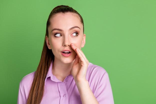 興味のある女の子の肖像画は、手の口の唇を見てコピースペースを共有しますささやきプライベートメッセージは、緑色の背景の上に分離された紫色のシャツを着ます