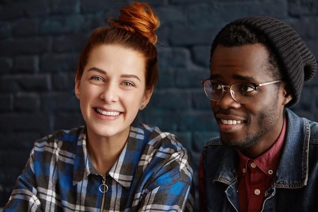 幸せな赤毛の白人女性とスタイリッシュなアフリカの男性の異人種間の若いカップルの肖像画