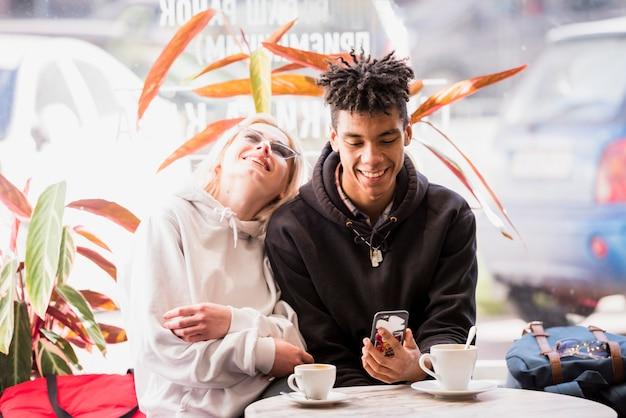 Портрет межрасовые молодая пара, сидя в кафе на открытом воздухе