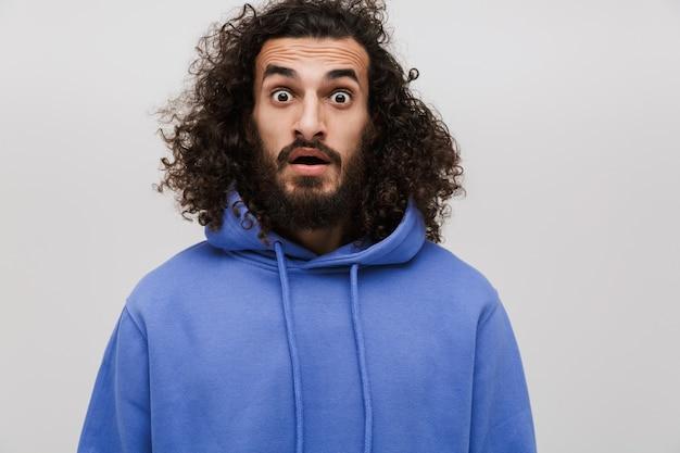 흰색으로 격리된 경이를 표현하는 캐주얼 스웨터를 입은 겁에 질린 면도하지 않은 남자의 초상화