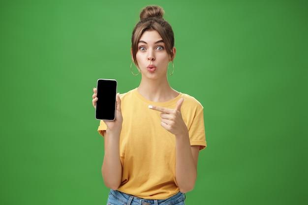 興味をそそられた女性の肖像画は、電話を保持している新しいスマートフォンを使用するのを待つことができません