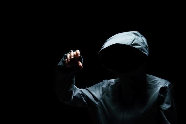 Портрет человека-невидимка в капюшоне на черном фоне.