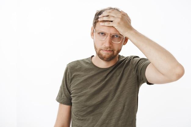 イライラしてイライラする若いビジネスマンのメガネと暗い緑色のtシャツの肖像画
