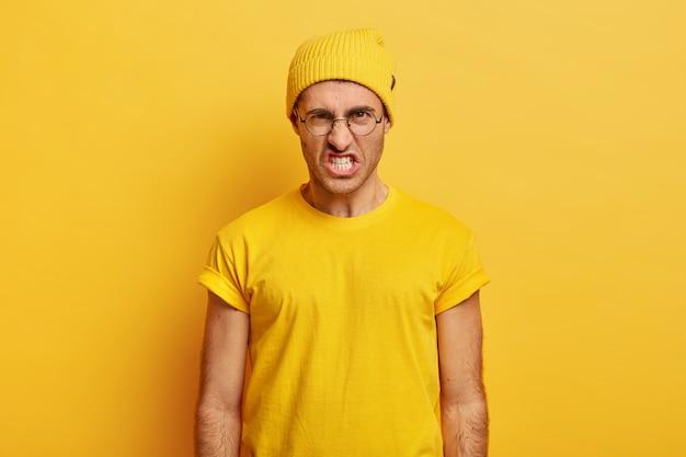 Портрет раздраженного мужчины выходит из себя, стиснет зубы от злости, морщит нос, с ненавистью смотрит в камеру, говорит, что вы меня бесите