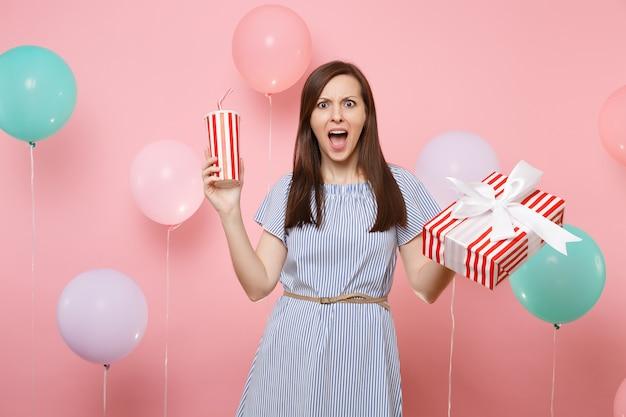 파란색 드레스를 입고 선물 선물이 든 빨간색 상자와 파스텔 핑크색 배경에 플라스틱 컵의 소다 또는 콜라를 들고 있는 충격을 받은 여성의 초상화. 생일 휴일 파티 개념입니다.
