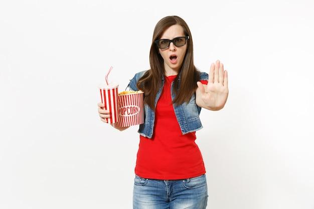 映画フィルムを見ている3dメガネでイライラした女性の肖像画、ポップコーンのバケツ、ソーダまたはコーラのプラスチックカップを保持し、白い背景で隔離の手のひらで停止ジェスチャーを示しています。映画の感情。