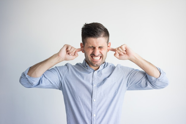 Портрет раздраженный молодой человек, забивая уши пальцами.