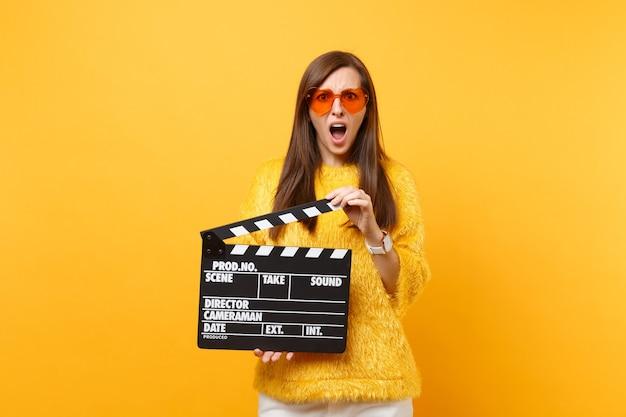 黄色の背景で隔離のカチンコを作る古典的な黒いフィルムを保持している毛皮のセーターオレンジハートグラスでイライラした若い女性の肖像画。人々は誠実な感情のライフスタイル。広告エリア。