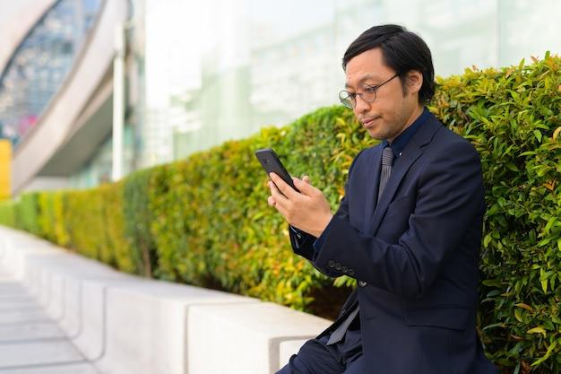 Портрет японского бизнесмена на свежем воздухе с природой в городе на открытом воздухе
