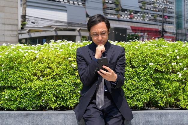 Портрет японского бизнесмена на свежем воздухе с природой в городе