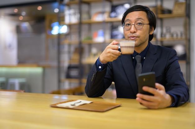 コーヒーショップの中に座っている日本のビジネスマンの肖像画