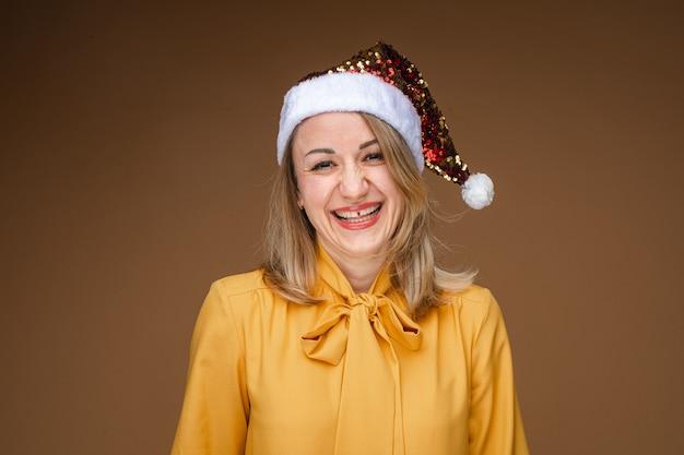 반짝이 산타 모자를 쓰고 노란색 블라우스에 유쾌한 금발 백인 여자의 초상화